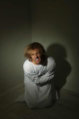 Mentally ill man in strait-jacket in room corner Stock Photo