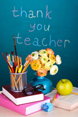 School supplies and flowers on blackboard with inscription Thank you teacher photo