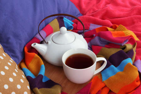 stand teapot: Cup and teapot on wooden stand and scarf on bed close up Stock Photo