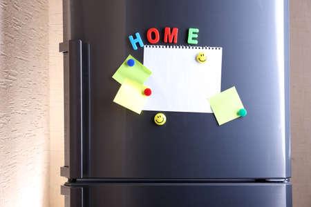 magnets: Empty paper sheets on fridge door Stock Photo