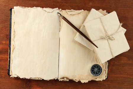 Open old book, letters and compass on wooden background photo