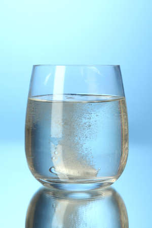 Glass with efervescent tablet in water with bubbles on blue background photo
