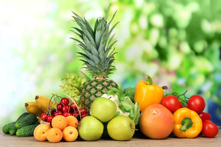 Assortment of fresh fruits and vegetables on natural background photo