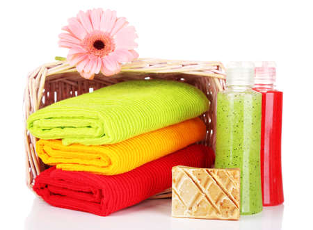 Colorful towels in basket cosmetics bottles and soap, isolated on white photo