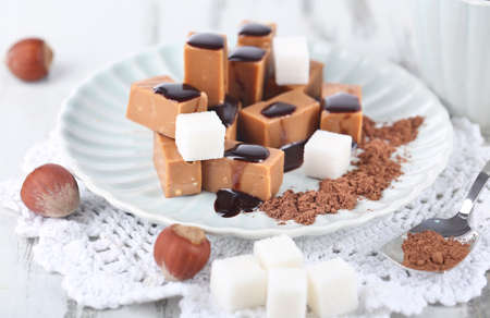 Many toffee on plate and cup of tea on napkin on wooden table photo