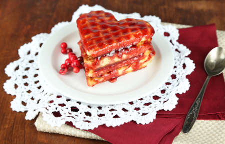 Sweet Belgium waffles with jam, on wooden table background photo