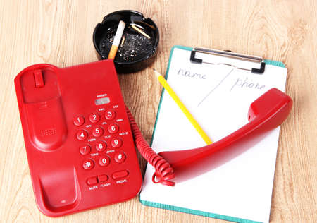 Telephone and notepad and other items, on wooden background photo