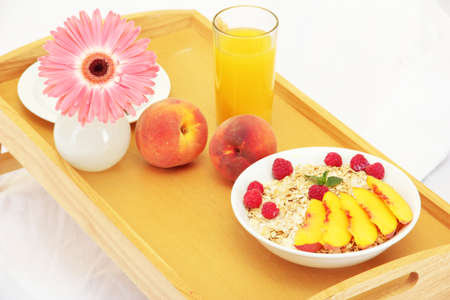wooden tray with light breakfast on bed, close up photo