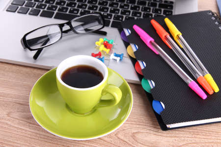 Laptop with stationery and cup of coffee on table photo