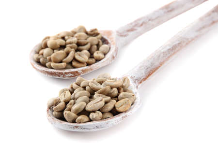 Green coffee beans in wooden spoons isolated on white photo
