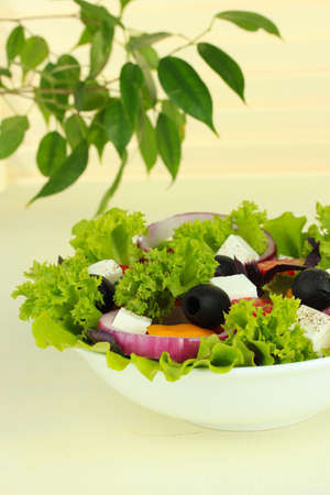 Greek salad on plate on table on light background photo