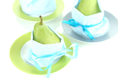 Pears in napkins on plates isolated on white photo