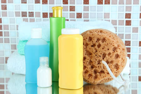 wisp: Cosmetics and bath accessories on mosaic tiles background Stock Photo