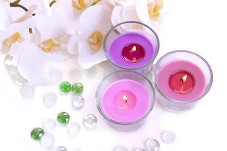 Beautiful colorful candles and orchid flowers, isolated on white photo