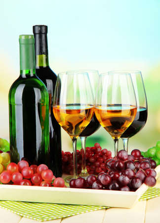 Wine bottles and glasses of wine on tray, on bright background photo