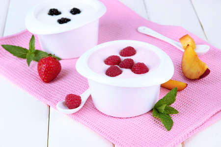 Delicious yogurt with fruit and berries on table close-up photo