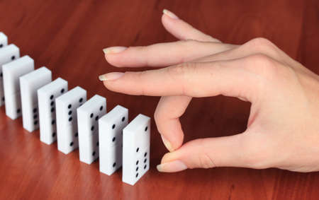 chain reaction: Hand pushing dominoes on wooden background Stock Photo