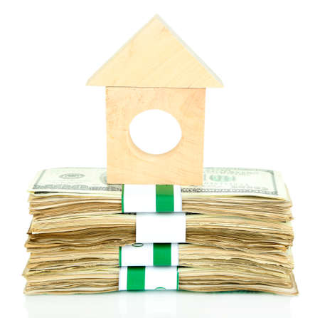 Wooden house on packs of dollars isolated on white Stock Photo - 24996062