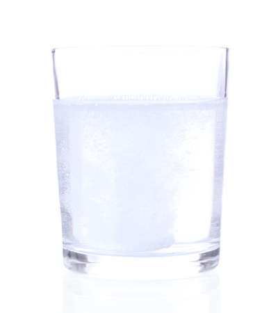 Glass with efervescent tablet in water with bubbles isolated on white photo
