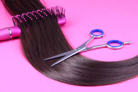 Long brown hair with hairbrush and scissors on pink background photo