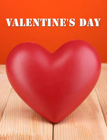 Decorative red heart on wooden table on orange background photo