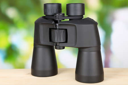 Black modern binoculars on wooden table on green background photo