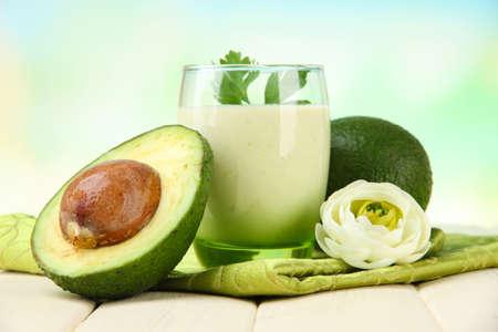 Fresh avocado smoothie on bright background photo