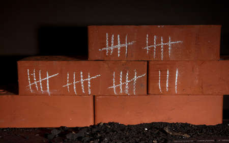 Counting days by drawing sticks on bricks on dark background photo