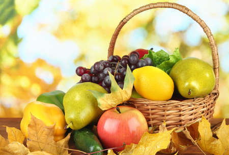 Different fruits and vegetables with yellow leaves in basket on table on bright background photo