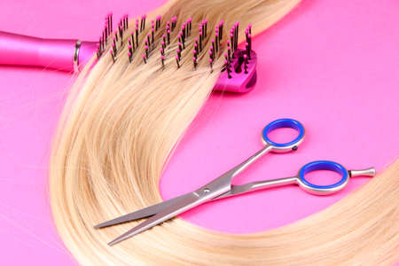 Long blond hair with hairbrush and scissors on pink background photo