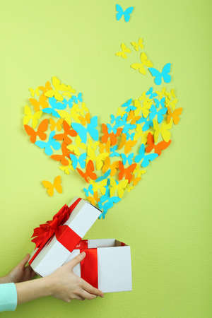 Paper butterflies fly out of box on green wall background photo