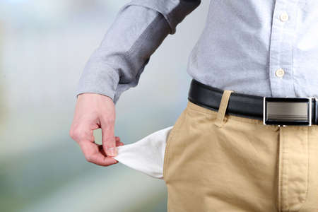 empty pocket: Man showing his empty pocket on bright background Stock Photo
