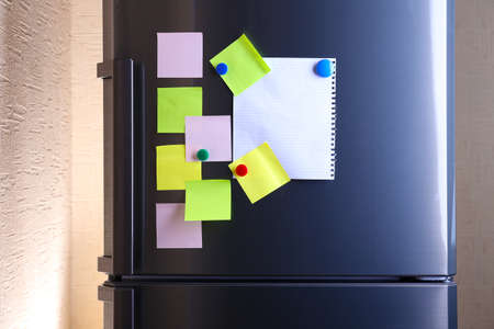 fridge: Empty paper sheets and colorful magnets on fridge door
