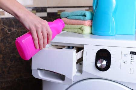 overburden: Female hands poured powder in washing machine close-up