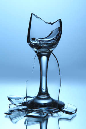 Broken wineglass on blue background photo