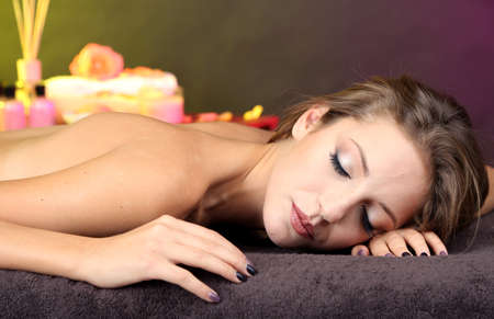 Beautiful young woman on massage table in cosmetic salon on color background Stock Photo - 25047611