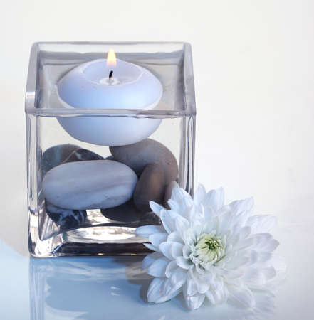 Decorative vase with candle, water and stones on light blue background photo