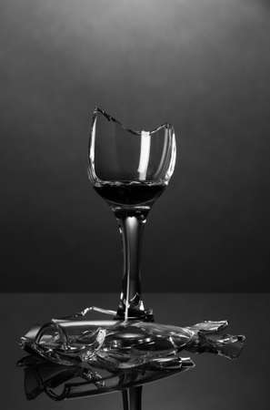 Broken wineglass on grey background photo