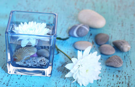 Decorative vase with flower, water and stones on wooden table close-up photo