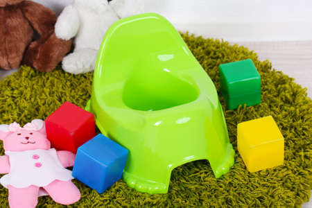 poo: Green potty on home interior background