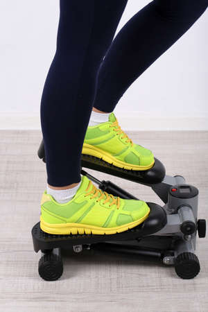 Woman doing exercise on stepper. Close-up on legs.  photo