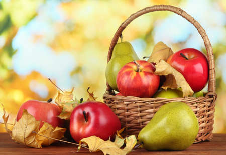 Beautiful ripe apples and pears with yellow leaves in basket on table on bright background photo