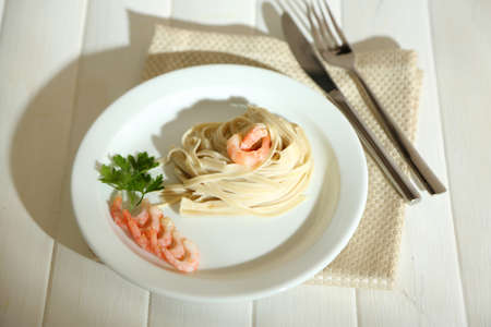 Pasta with shrimps on white plate, on wooden background photo
