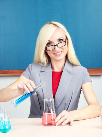 Chemistry teacher with tubes sitting at table on blackboard background photo
