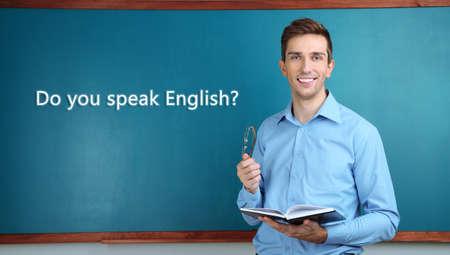 učit se: Mladý učitel u tabule ve školní třídě Reklamní fotografie