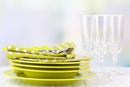 Clean dishes on wooden table on light background