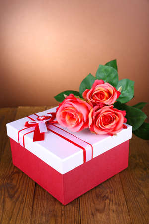 Beautiful gift box with flowers on table on brown background photo