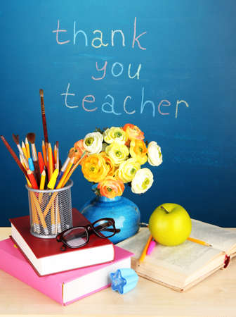 School supplies and flowers on blackboard background with inscription Thank you teacher photo