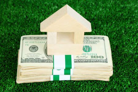 Wooden house on packs of dollars on grass close-up Stock Photo - 25128330