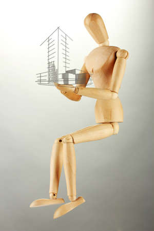 unfinished: Wooden mannequin with house sketch project , on grey background